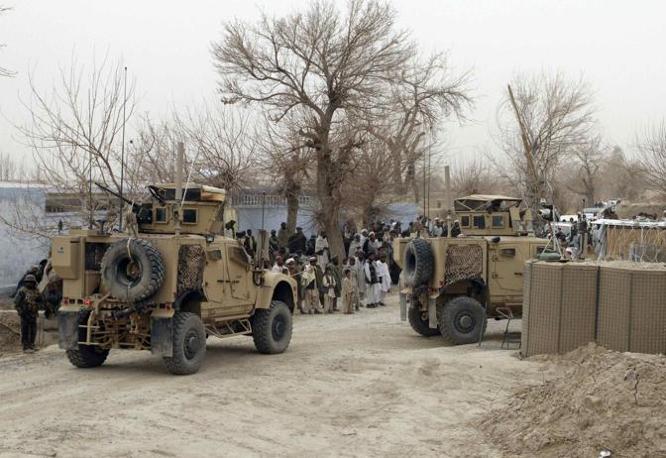 Veicoli corazzati dell'esercito americano fuori della base di Panjwai, nel distretto di Kandahar, osservano i locali radunarsi (Reuters/Ahmad Nadeem)