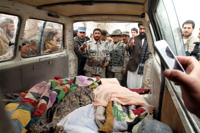La polizia afghana e decine di civili intorno al furgone con i corpi delle vittime (Epa/I. Sameem)