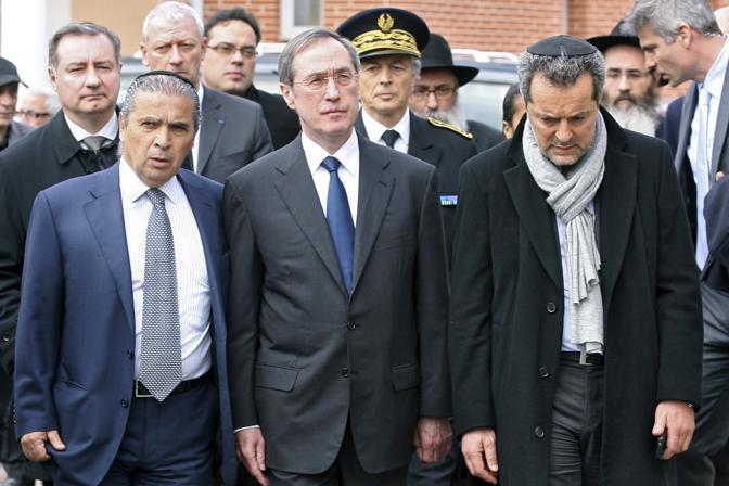 Il ministro degli Interni francese Claude Gueant, al centro, rende omaggio alle vittime (Reuters)
