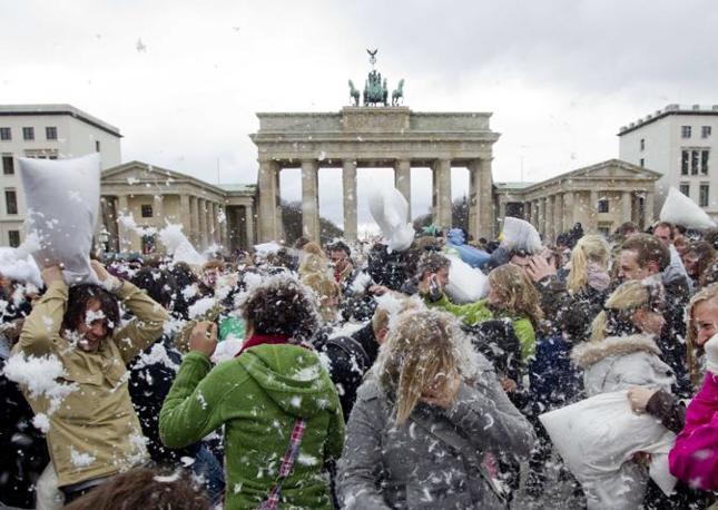 """Ragazzi e ragazze si prendono a """"cuscinate"""" durante un flash mob davanti alla porta di Brandeburgo a Berlino (Reuters/Peter)"""