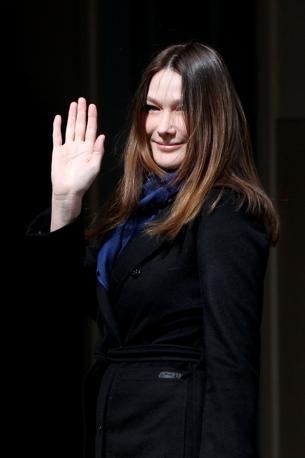 La first lady Carla Bruni saluta i sostenitori all'arrivo al seggio (AFP)