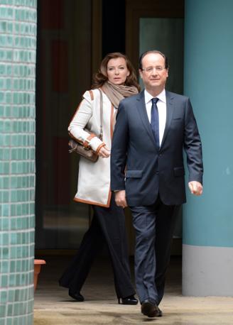 Hollande all'uscita dal seggio con la compagna Valérie Trierweiler, giornalista (Afp)