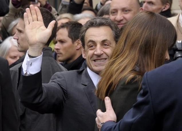 Sarkozy e Carla Bruni all'uscita del seggio a Parigi (Epa)