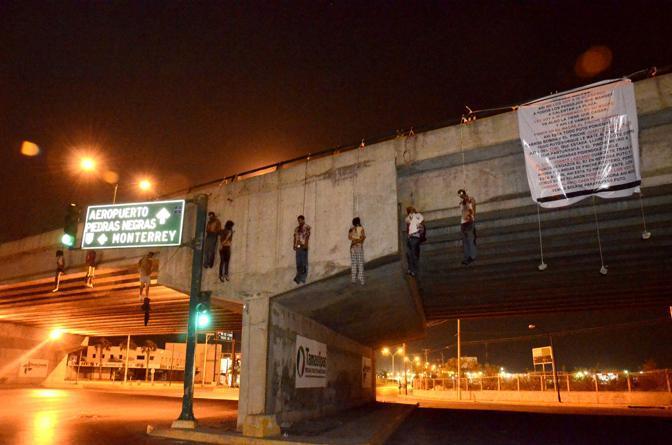 Le vittime prima sono state pestate a sangue e poi impiccate. Su un lenzuolo il cartello dei Los Zetas hanno scritto il loro comunicato dove accusano le vittime di appartenere alla banda rivale del Golfo (Afp/Llamas)