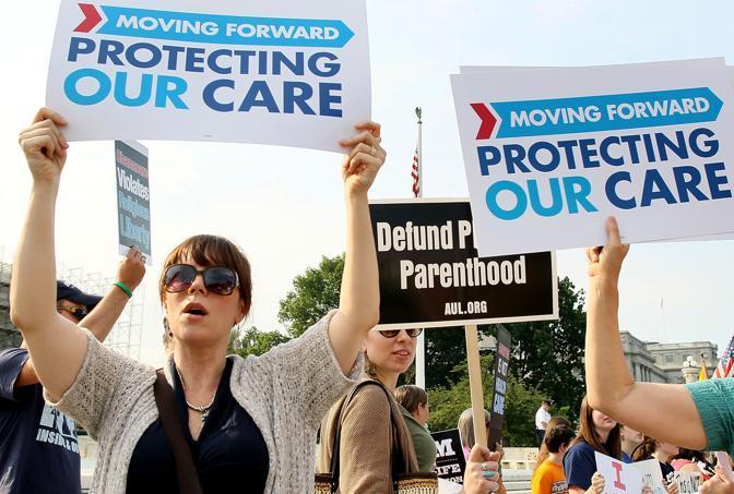 Manifestazione mista. Sostenitori di Obama in primo piano, oppositori di sfondo (Getty Images/Afp)