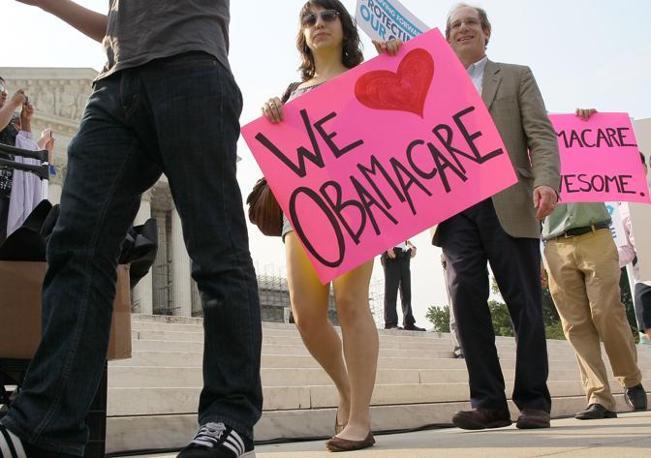 «Amiamo l'obamacare» e, sullo sfondo, «l'obamacare è meravigliosa» (Afp)