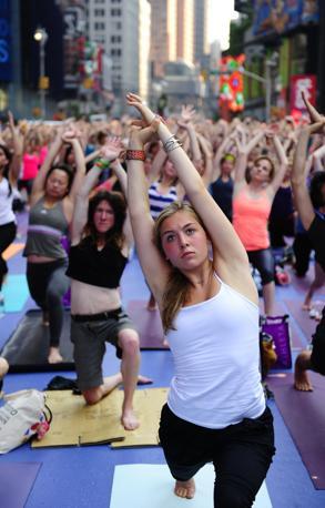 Migliaia di persone hanno salutato il solstizio d'estate facendo... yoga a Times Square, nel cuore di New York (Afp)