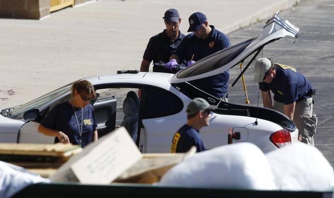 L'Fbi vicino alla macchina di Jmaes Holmes: l'uomo è stato fermato proprio mentre cercava di allontanarsi dal cinema in auto (Ap/Zalubowski)