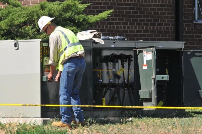Operai dell'azienda elettrica «tagliano i fli» alla casa di Holmes per ridurre il rischio di esplosioni (Afp)