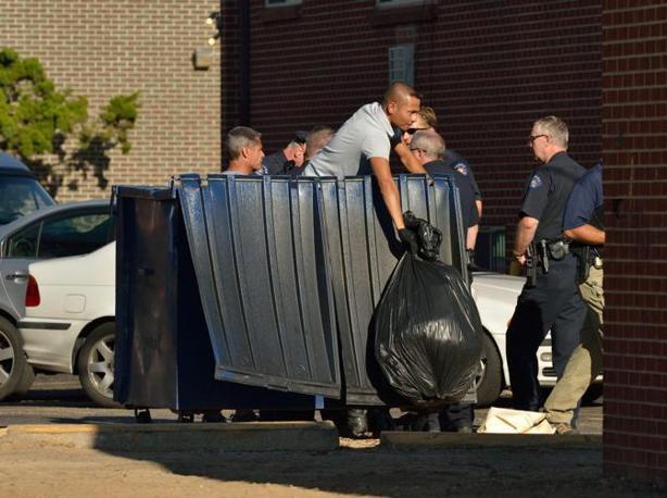 La polizia fruga nell'immondizia all'esterno dell'appartamento di Holmes (Epa)