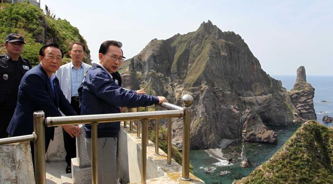 "Il presidente Lee Myung-Bak durante la visita pone una targa su un monumento con la scritta ""territorio coreano"". (Afp)"