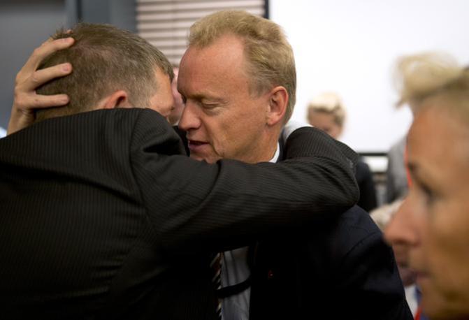 Il segretario del partito laburista norvegese, Raymond Johansen, abbraccia il famigliare di una vittima dopo la sentenza di colpevolezza (Afp)