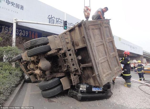 La gru solleva l'autocarro che ha schiacciato l'automobile (China News)