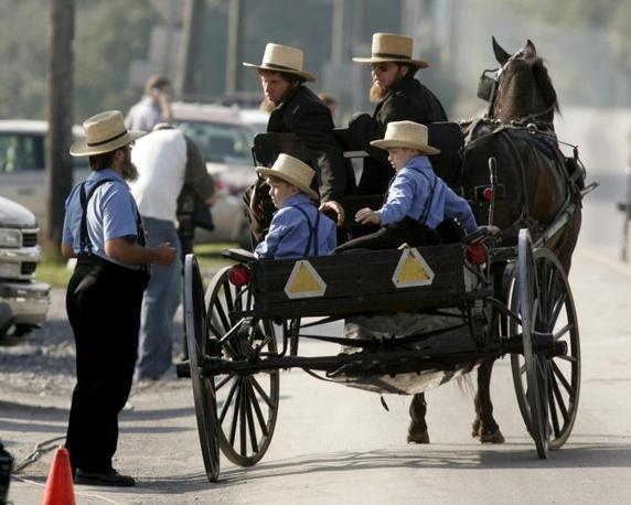 3 ottobre 2006 - Pennsylvania: un gruppo di Amish in Pennsylvania parlano accanto alla casa di una delle vittime della sparatoria avvenuta in una scuola Amish. (Epa/Cavanaugh)