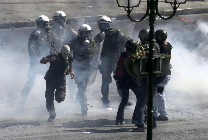 La polizia ha risposto con lanci di gas lacrimogeni e cariche. Un manifestante con maschere antigas tenta la fuga (Ap/D. Messinis)