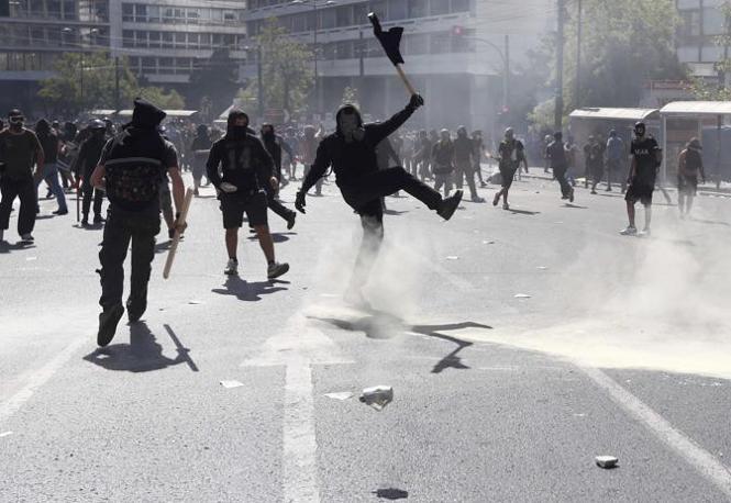 Un dimostrante con la bandiera nera allontana una bombola di gas lacrimogeno con un calcio (Reuters/Karahalis)