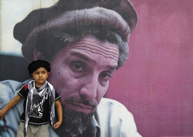 Un ragazzino afghano posa vicino a una foto del comandante Massoud, eroe della guerra contro l'Urss (Reuters)
