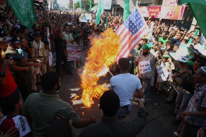 Scontri e proteste anche in Palestina. A Rafah, nella striscia di Gaza, i manifestanti hanno dato alle fiamme la bandiera americana (Afp)