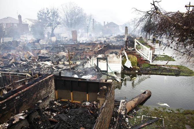 Dozzine di edifici devastati dalle fiamme a Breezy Point, nel quartiere di Queens, a New York. Qui si sono verificate le devastazioni maggiori, non soltanto per l'inondazione di vaste aree ma anche per gli incendi causati dalla caduta di pali della corrente elettrica: sono circa 80 le case incendiate nel quartiere  (Ramin Talaie /Ansa)