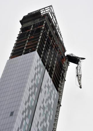 La gru semisistrutta nella parte più alta ha per fortuna retto nel resto della struttura accanto a un nuovo rattacielo in completamento a Midtown, New York (Timothy A. Clary /Afp)