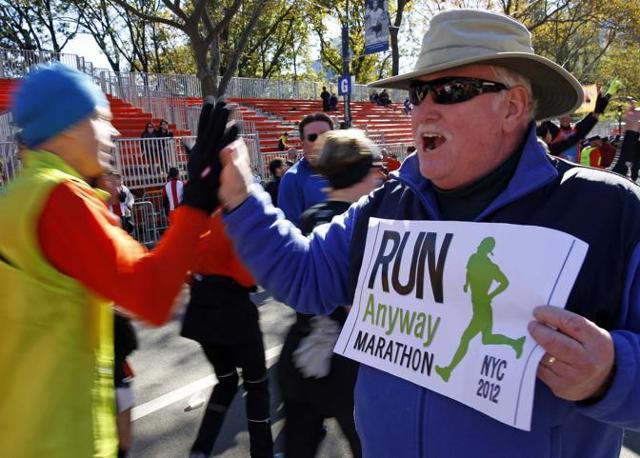 In centro c'è anche chi fa il tifo. Il cartello recita: «Corriamo comunque - Maratona Nyc 2012» (Reuters/East)