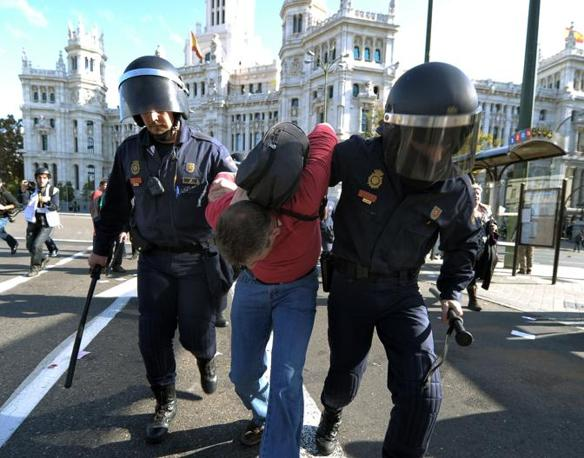 Un manifestante fermato a Madrid (Afp/Lluis Gene)