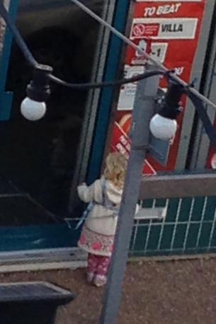 Una donna lega la figlia al guinzaglio fuori da un negozio di scommesse: la bimba cerca di liberarsi, sotto lo sguardo esterrefatto dei passanti, invano (Milestone Media)