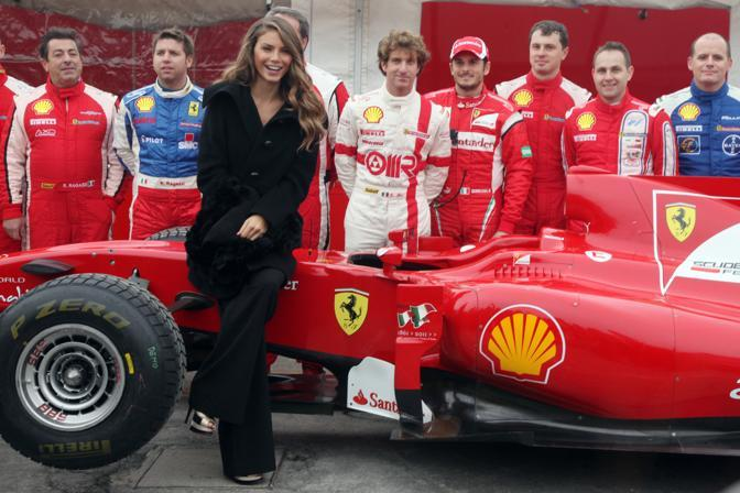 La modella Nina Senicar al Motorshow 2011 con il pilota di F1 Giancarlo Fisichella e il suo team (Ansa)