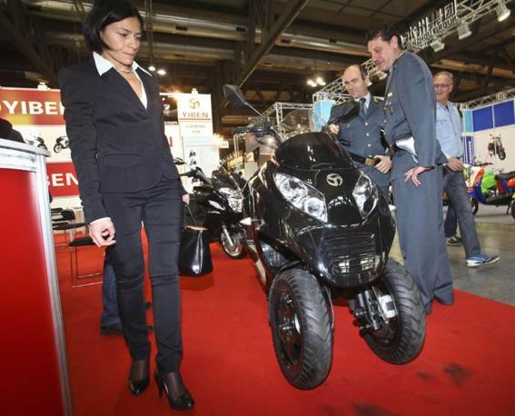 La Guardia di Finanza fra gli stand del Salone del motociclo a Milano per portare via un tre ruote prodotto dai cinesi della Kaitong Motors e considerato troppo simile al Piaggio MP3.