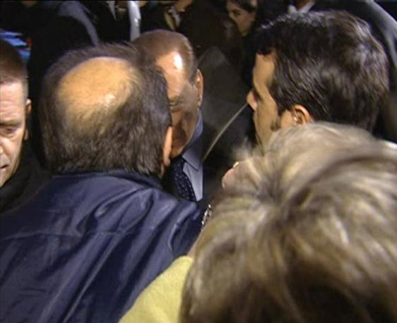 Silvio Berlusconi è stato colpito al volto con una statuetta souvenir in Piazza Duomo a Milano. L'aggressore, un 42enne con problemi psichici, è stato arrestato. Il premier ha riportato una frattura del setto nasale ed è stato ricoverato al San Raffaele. Il fermo immagine, tratto dal TG- LA7 mostra il presidente del Consiglio Silvio Berlusconi mentre è colpito al volto. Il premier si è subito accasciato, è stato fatto sedere all'interno della sua vettura dalle guardie del corpo, ma poi  è tornato un attimo fuori dall'auto per farsi vedere, prima di risalire sulla macchina ed essere trasportato in ospedale (Ansa)