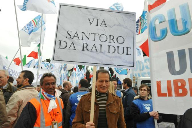 Cartello contro Michele Santoro alla manifestazione nella Capitale (Ansa)