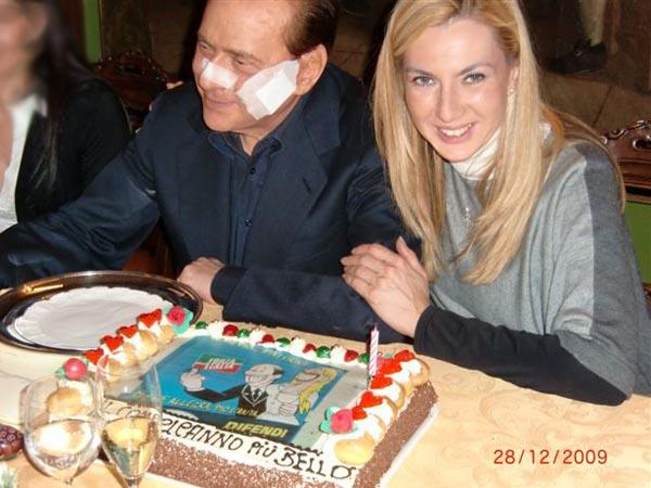 Michaela Biancofiore durante il suo compleanno, ad Arcore con Silvio Berlusconi. Sulla torta, che ha portato lei, la vignetta che ricorda il comizio del Presidente a Bolzano nel 2005 (Ansa)