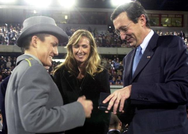2003, Gianfranco Fini consegna un omaggio a una delle atlete che prenderanno parte ai Giochi Mondiali Militari durante la cerimonia inaugurale a Catania. Al centro la Prestigiacomo (Ansa)