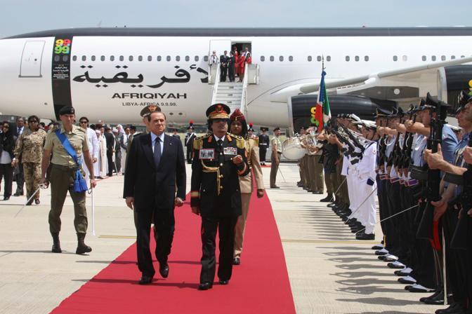 Il Presidente del Consiglio Silvio Berlusconi accoglie il leader libico Muammar Gheddafi che porta la celebre foto sul petto (Ansa)