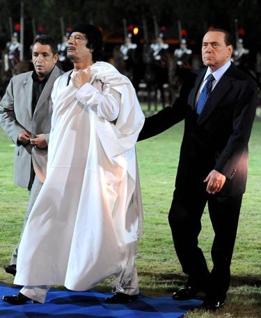 Il leader libico Muammar Gheddafi e il presidente del Consiglio Silvio Berlusconi durante la cerimonia nella caserma Salvo D Acquisto di Roma nel 2010 (Ansa)