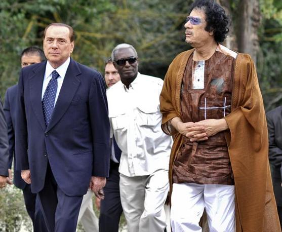 Il presidente del Consiglio Silvio Berlusconi ed il leader libico Muammar Gheddafi entrano nell Accademia libica in Italia a Roma nel 2010 (Ansa)