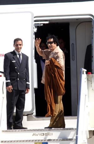 Gheddafi saluta dalla scaletta dell'aereo all'aeroporto di Ciampino (Ansa)