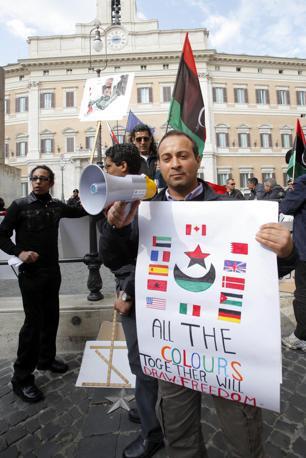A Roma, in piazza Montecitorio.  sventolano le bandiere verde-rosso-nere con mezza luna e croce bianca della Libiam pre-Gheddafi (LaPresse)