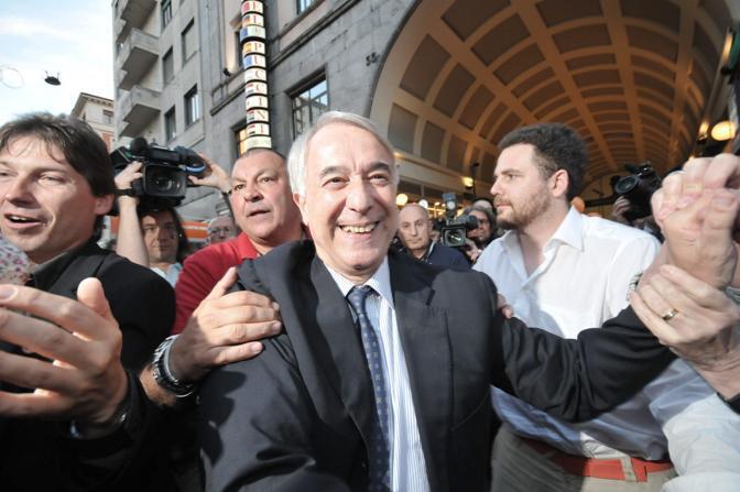Giuliano Pisapia, candidato per il centrosinistra a Milano, saluta la gente davanti alla sede del suo comitato elettorale (Fotogramma)