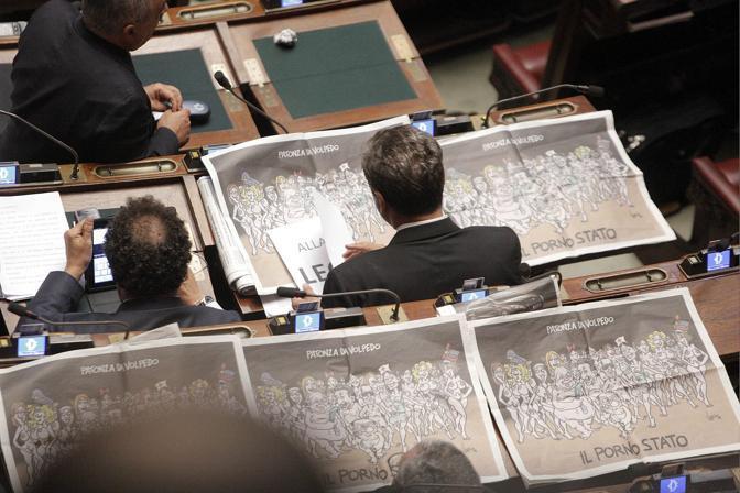 La Camera si prepara a votare la mozione di sfiducia sul ministro Saverio Romano e i deputati Fli   protestano contro il premier esponendo la vignetta di Vauro dedicata a «Il porno stato» (Ansa)