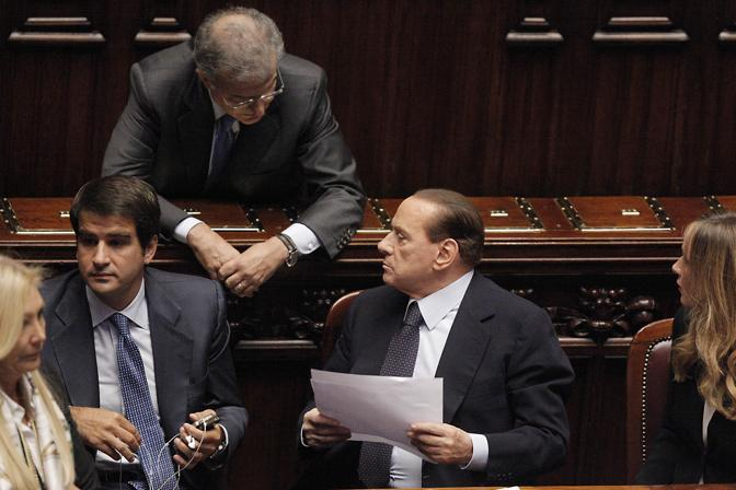 Il capogruppo del Pdl Fabrizio Cicchitto si avvicina al banco del governo per parlare con Berlusconi (Ansa/Lami)