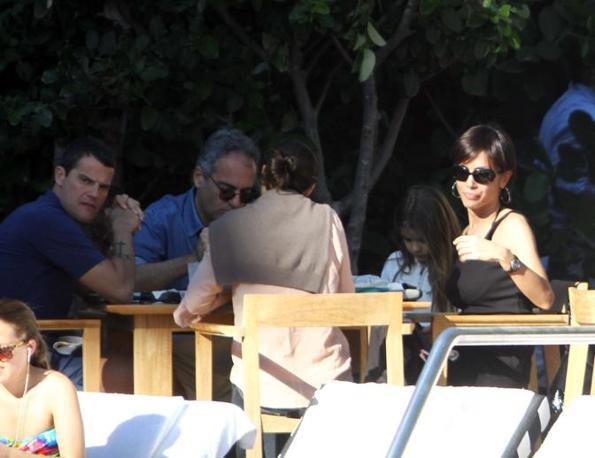 Mara approfitta del  pranzo in compagnia di amici per  scoprire le spalle e godersi ancora un po'  di sole. A capotavola il marito (Olycom)