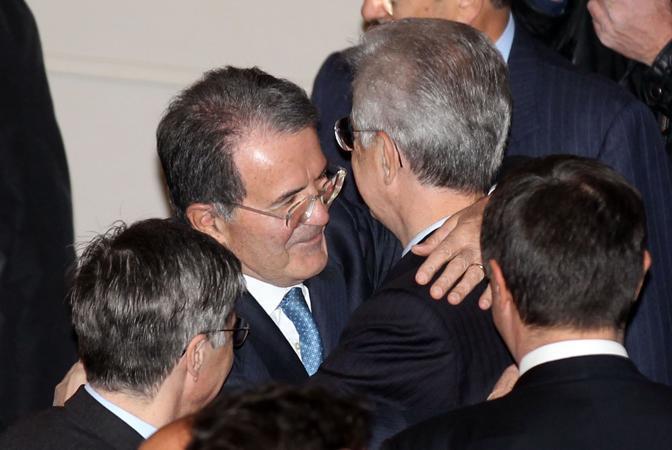 Il presidente del Consiglio Mario Monti e l'ex premier Romano Prodi si abbracciano al teatro Valli di Reggio Emilia, durante le celebrazioni per il 215° anniversario del primo Tricolore (ANSA)
