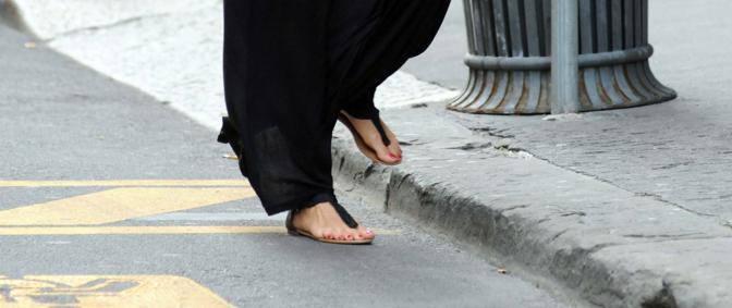 Un tocco di vanità anche per i piedi: infradito e smalto rosso (Olycom)
