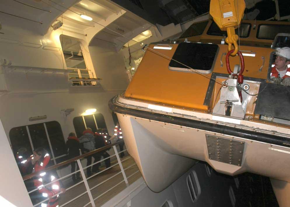 Passeggeri in fuga sul ponte della nave gi� inclinata: in primo piano uno dei battelli di salvataggio  mentre viene calato in acqua (Ansa)