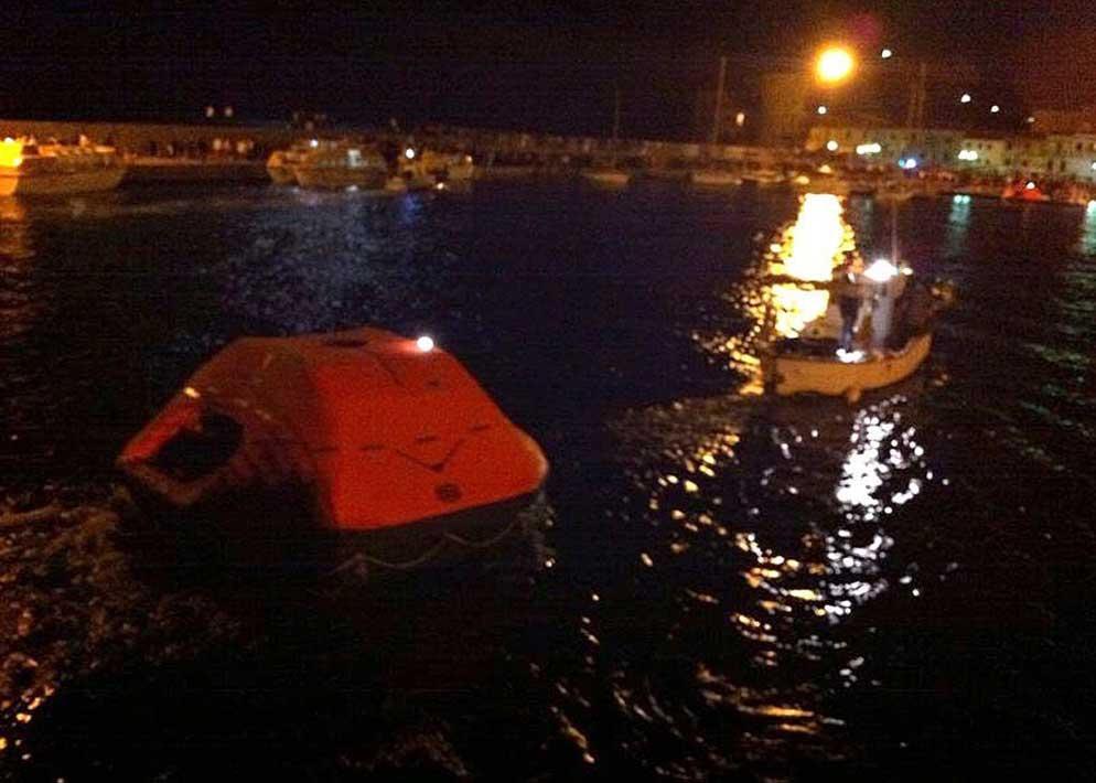 I battelli di salvataggio carichi di naufraghi entrano nel porto del Giglio (Epa)