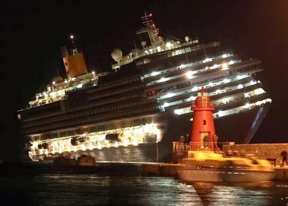 Un'immagine drammatica della gigantesca nave inclinata di fronte alla banchina del porto (Ap)