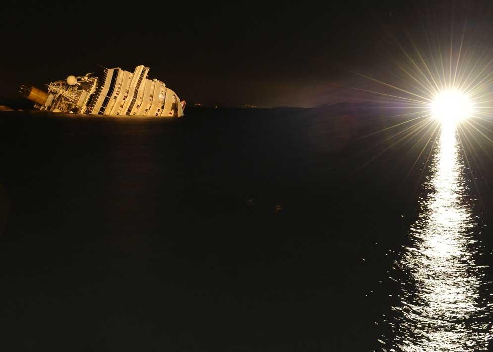 Solo la luce di un fanale illumina la carcassa della Concordia in una visione notturna davvero spettrale (Italyphotopress)