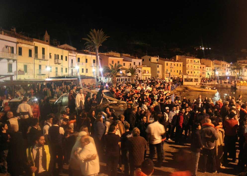 Folla nel porto del Giglio, gli abitanti del posto sono stati i primi ad accogliere i naufraghi e a fornire loro assistenza (Ansa)