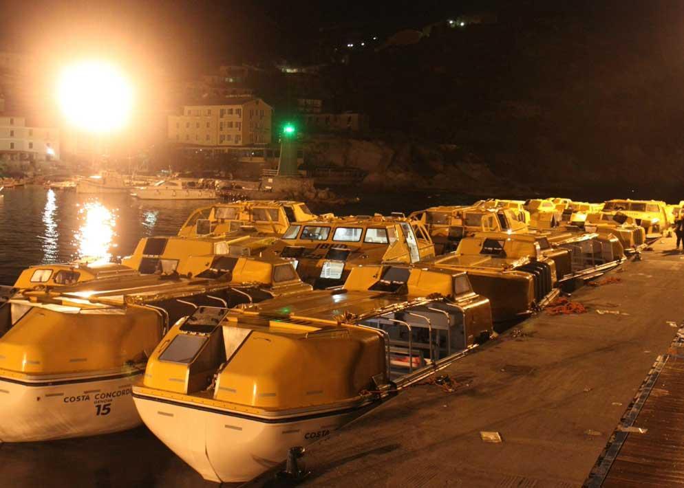 Una flotta di scialuppe gialle nel porto, sono quelle usate dai passeggeri della Concordia per mettersi in salvo (Ansa)